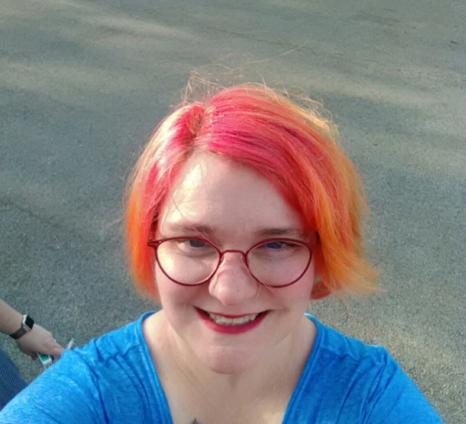 Image of the author with bright sunset-colored hair, red glasses and a big smile. And also a blue shirt.